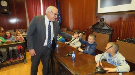 El alcalde entrega su bastón de mando al alumno que ocupa su lugar en el salón de plenos