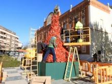 Operarios colocando los adornos reciclados para dar forma al árbol