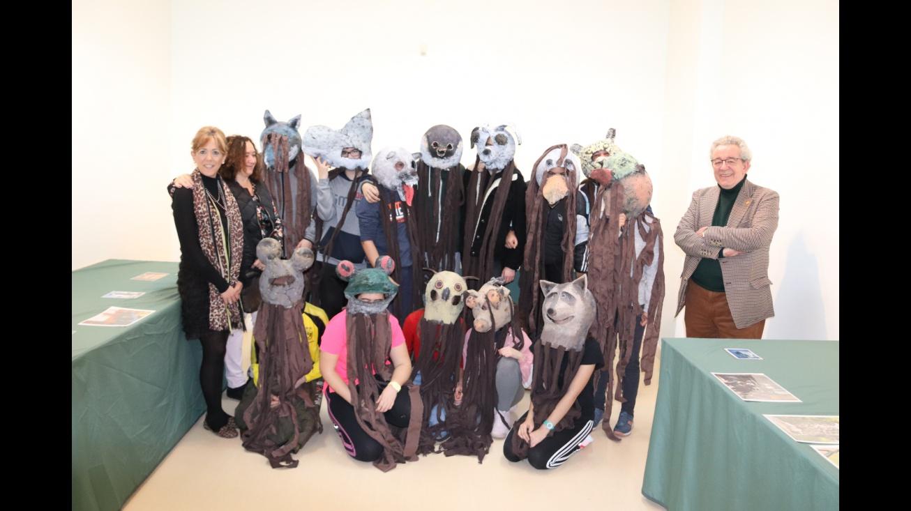 El alumnado posa con las máscaras de la exposición