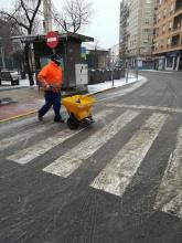 Un operario esparce sal en un paso de peatones en la zona del Gran Teatro