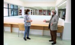 Candi Sevilla comprueba las medidas de distanciamiento en los puestos de estudio y lectura de la biblioteca junto a su directora