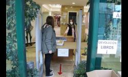 Entrega de libros a una usuaria en el mostrador habilitado a la entrada de la biblioteca